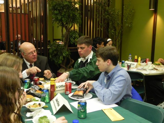 Commissioner Tom Middleton talks with students from Lake Orion High School over lunch