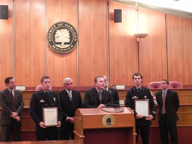 Pictured left to right are Vice Chairman Jeff Matis, Farmington Hills Inspector/Paramedic Bryan R. Hewitt, Farmington Hills Fire Chief Corey Bartse at podium, Oakland County Farmington Hills Jim Nash, Farmington Hills Inspector/Paramedic Ryan B. Munsell, Oakland County Commissioner Jim Nash and Oakland County Board Chairman Michael J. Gingell.