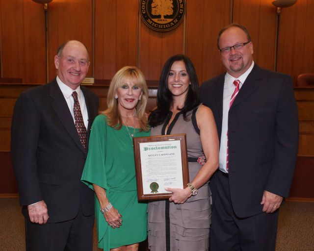 Pictured left to right are: Oakland County Commissioner Bob Hoffman, Maureen LaFontaine, mother of honoree Kelley LaFontaine holding proclamation, and Commissioner Jim Runestad.
